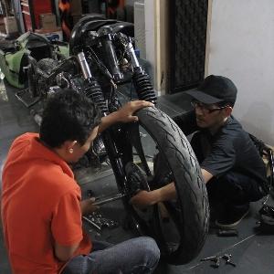 Salah seorang crew Imagineering Custom memasng as roda Harley-Davidson Road King Cafe Bagger